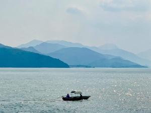 misty sky, hills, sea, anglers, boat